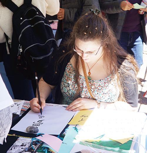 アクティビティーテントの一つで習字に挑戦する女性=同(撮影:高橋)