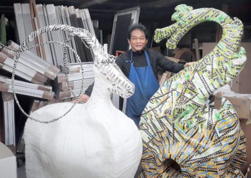 林世宝さんがメトロカードを使って制作中の龍(右)と羊